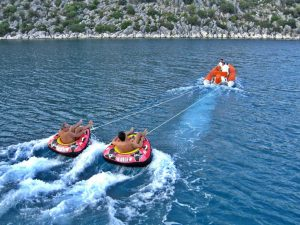 Tubing behind the tender watersports on a blue cruise